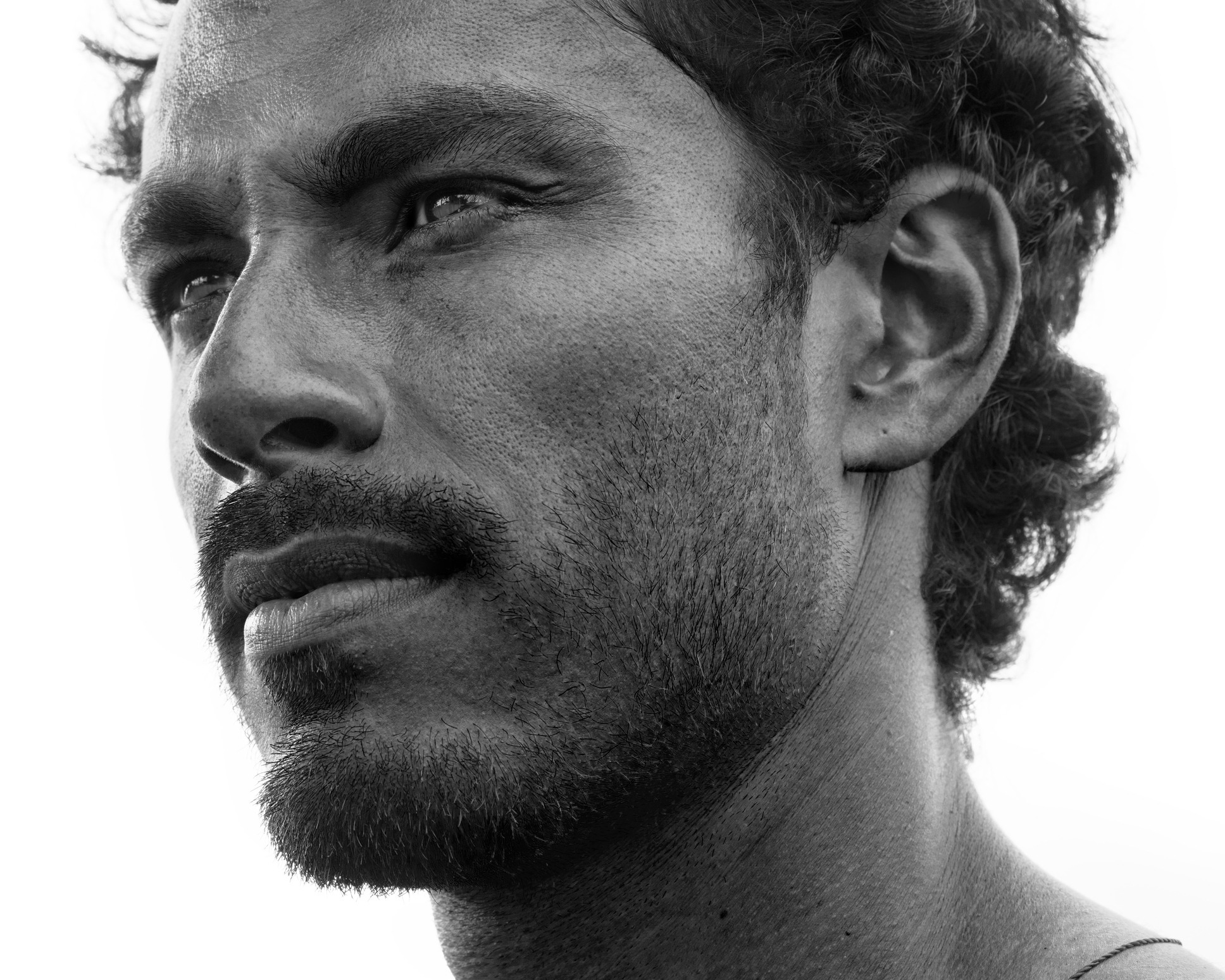 Close up portrait of healthy man with black hair, strong features, looking straight ahead at a three quarters angle, black and white